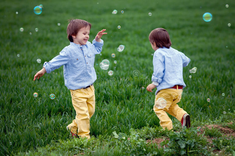 Two Boys, Running And Chasing Soap Bubbles Stock Photo