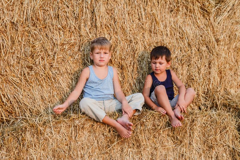 Two boys sit on the big barn. In autumn stock image