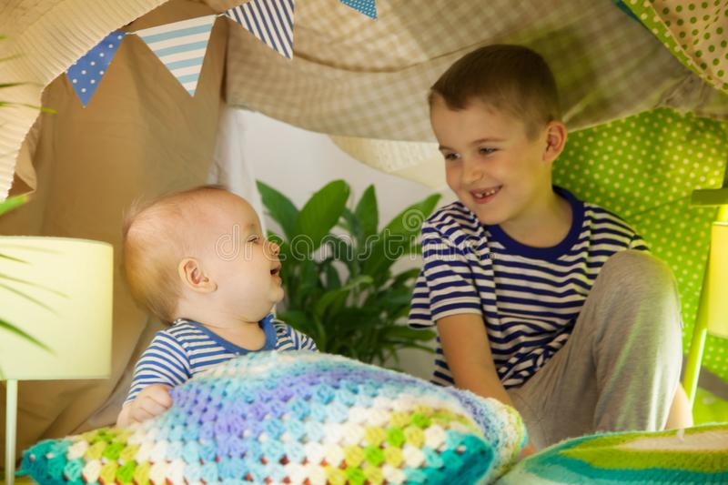 Two cute brothers play with a flashlight in a children`s tent. 6 years old boy and baby toddler stock photo