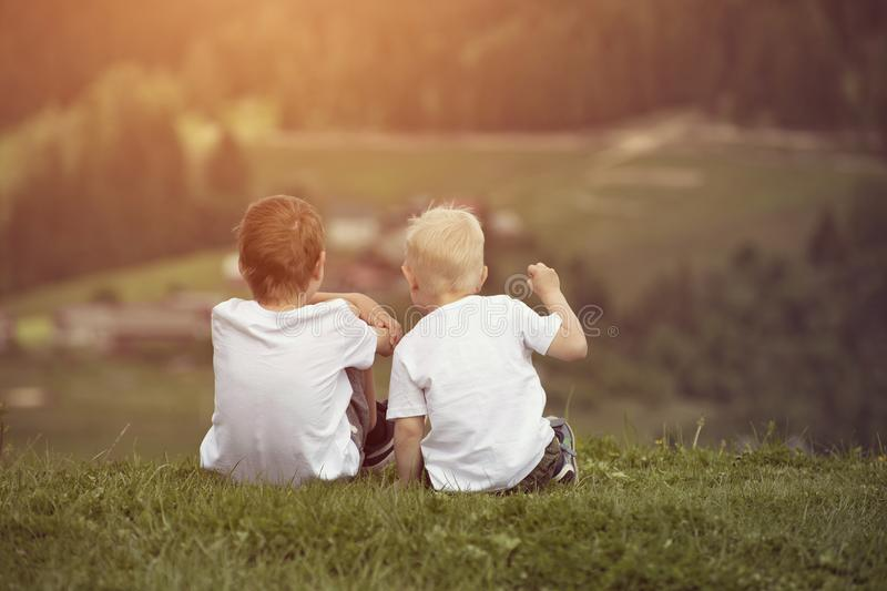 Two boys sit on the hill and talking cheerfully. Back view royalty free stock image