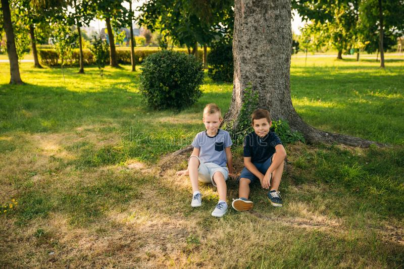 Two boys sits on grass near the tree. Eight year old children spend time in park royalty free stock image