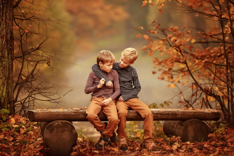 Two boys sitting on a bench by the pond. royalty free stock image