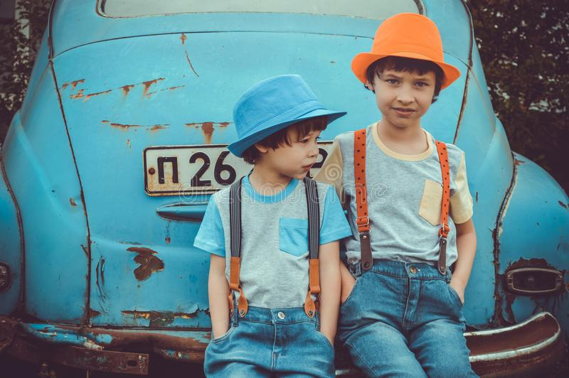 Two Boys Sitting on Blue Volkswagen Beetle Coupe's Rear Bumper royalty free stock photo