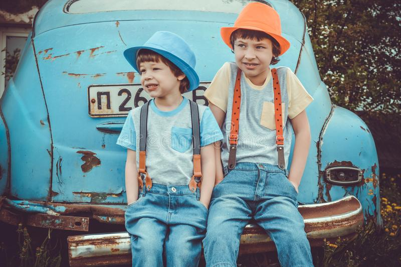 Two Boys Sitting on Classic Blue Car's Rear Bumper stock photo
