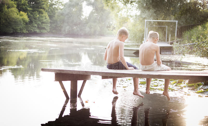 Two boys sitting on a pier royalty free stock photos