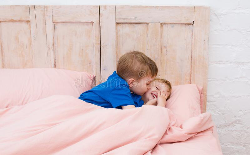 Two boys smiling under a blanket. Brothers kissing and playing. royalty free stock image