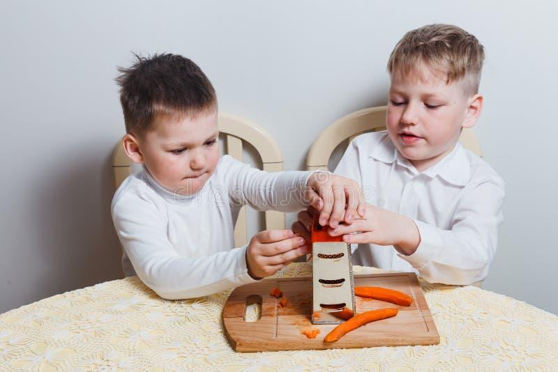 Two boys boiled carrots stock photos