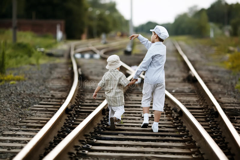 Two boys with suitcase on railways royalty free stock photography