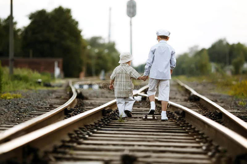 Two boys with suitcase on railways. Two happy boys with suitcase on railways royalty free stock photos