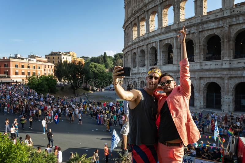 Two boys take a selfie in front of the Colosseum royalty free stock photo