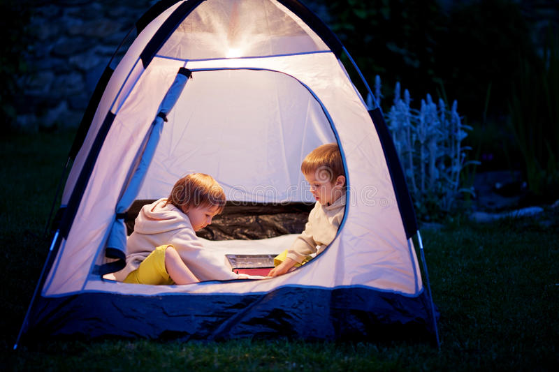 Two boys in a tent, playing chess stock photo