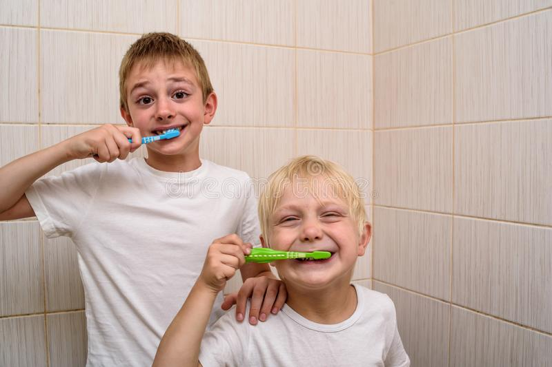 Two boys thoroughly brush their teeth in the bathroom. Morning hygiene royalty free stock photography