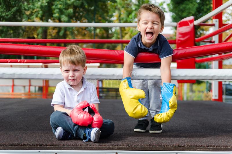 The joyful laughter of the winner and the bitter tears of the lo. Two boys three years in a boxing ring. Taste of victory. The joyful laughter of the winner and royalty free stock photos