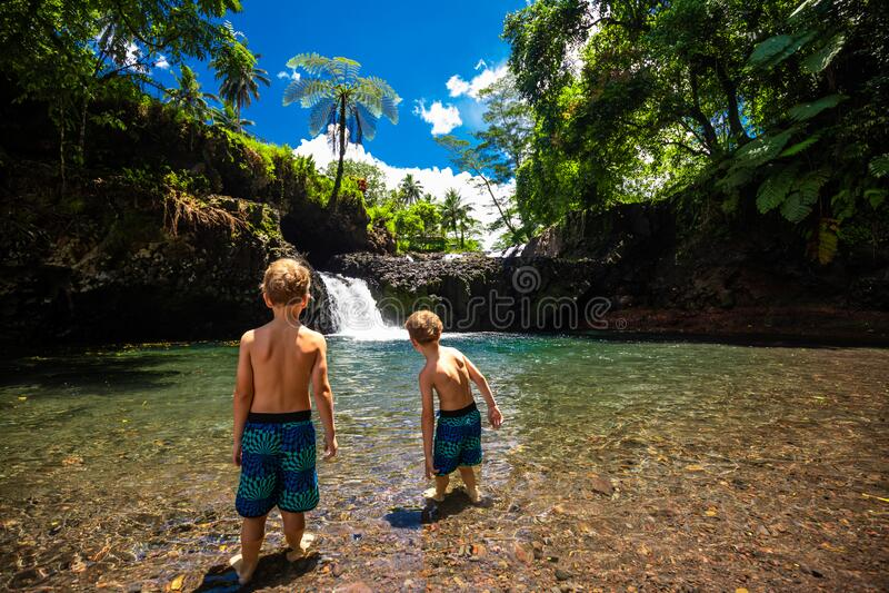 Two boys at Togitogiga falls with swimming hole on Upolu, Samoa royalty free stock image