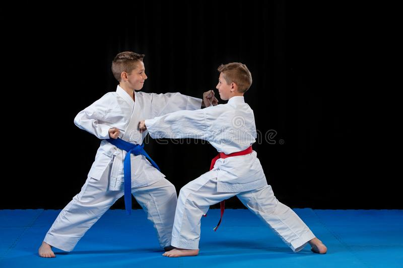 Two boys training karate kata exercises at test qualification.  stock photos