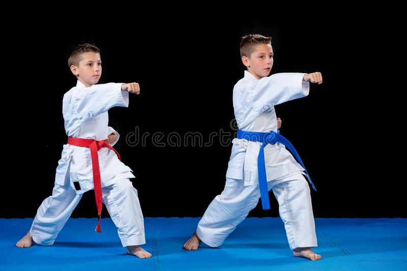 Two boys training karate kata exercises at test qualification.  stock images