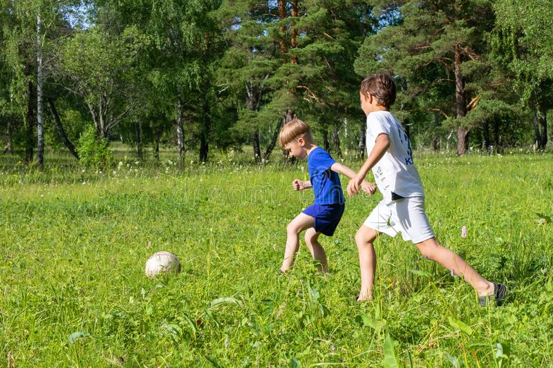 Two boys in uniform plays football on a meadow. Children run and kick a soccer ball. Summer outdoor games. Two boys in uniform plays football on a green meadow royalty free stock image