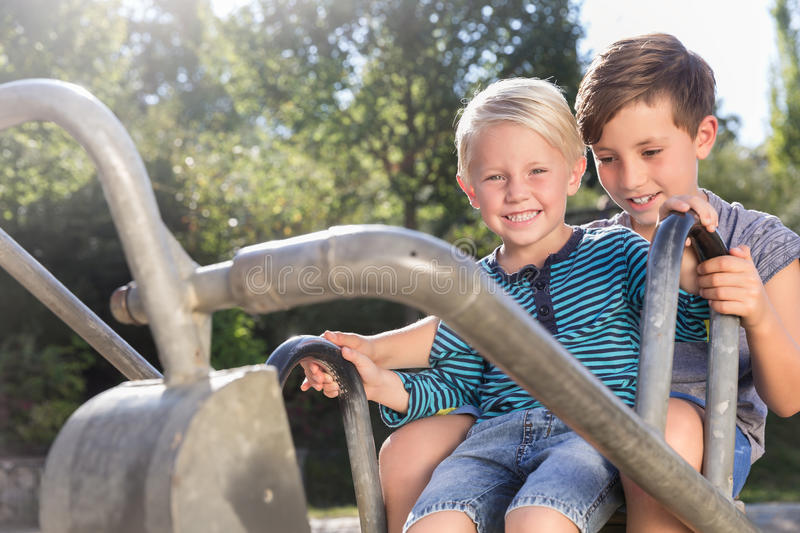 Two boys using digger on adventure playground in park stock photos