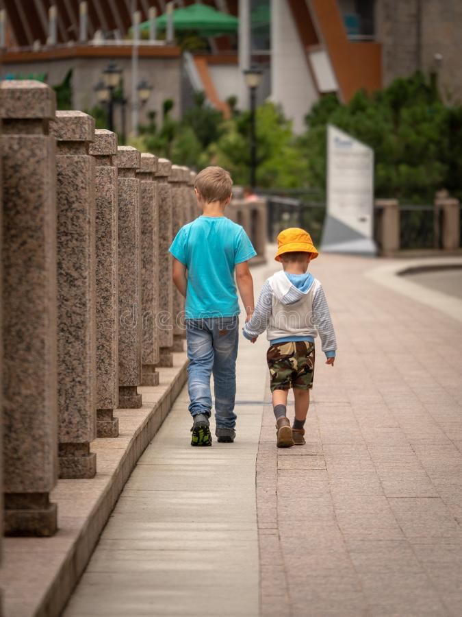 Two boys walk along the city river royalty free stock photos
