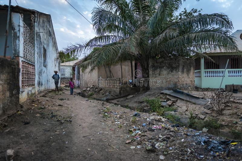 Two boys walking in a dirt street along an open sewer at the Cupelon de Baixo neighborhood in the city of Bissau. Bissau, Republic of Guinea-Bissau - January 31 stock photos