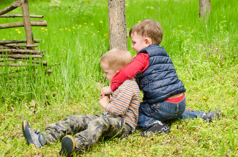 Two Boys Wrestling in the Grass royalty free stock image