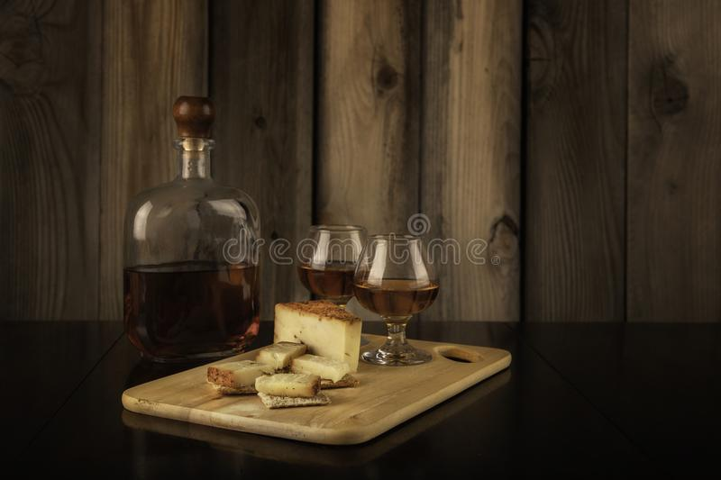 Two Brandy Snifters, Cheese Board and Bottle of Brandy royalty free stock images