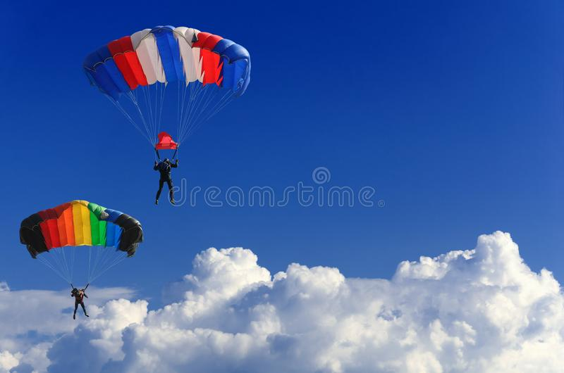 Two parachutists soar on colorful parachutes across the boundless blue sky against the background of white fluffy clouds. Two brave parachutists make a joint royalty free stock photography