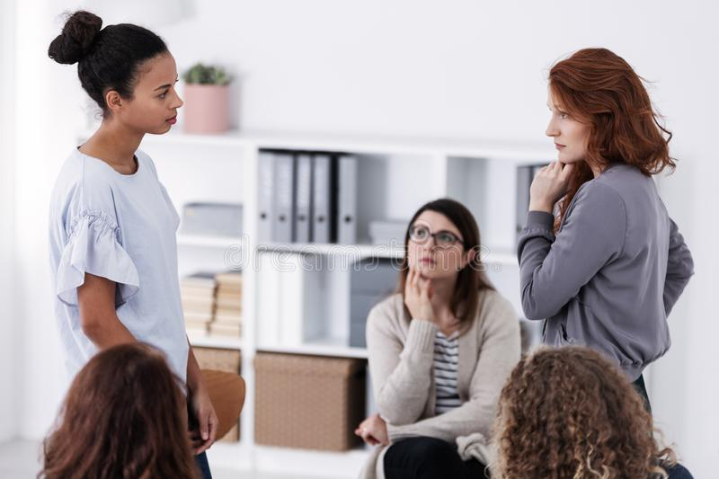 Two brave women standing and looking at each other during role paying at psychotherapy support meeting royalty free stock photo