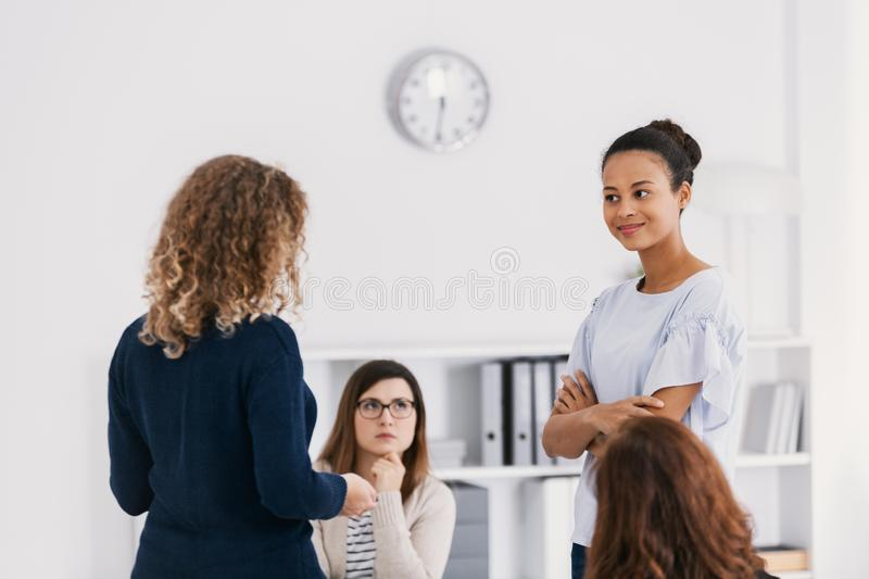 Two brave women standing and looking at each other during role paying at psychotherapy support meeting royalty free stock photography