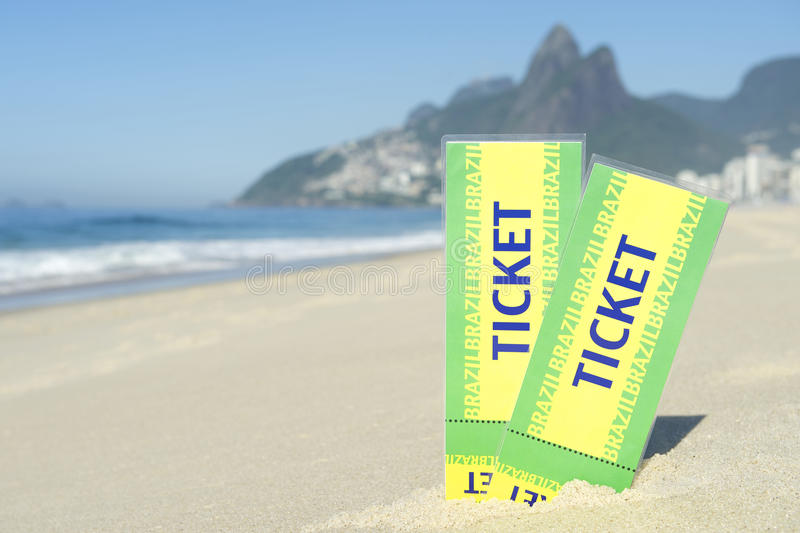 Two Brazil Tickets in the Sand Ipanema Beach Rio. Two large Brazil tickets in the sand on the Ipanema Beach in Rio de Janeiro with Dois Irmaos Mountain in the royalty free stock photos
