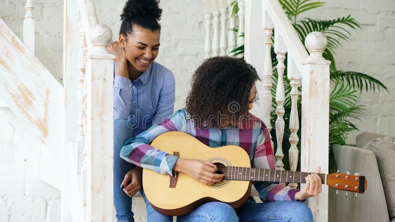 Two brazilian curly girls sistres sitting on stairs and practice to play acoustic guitar. Friends have fun and singing stock images