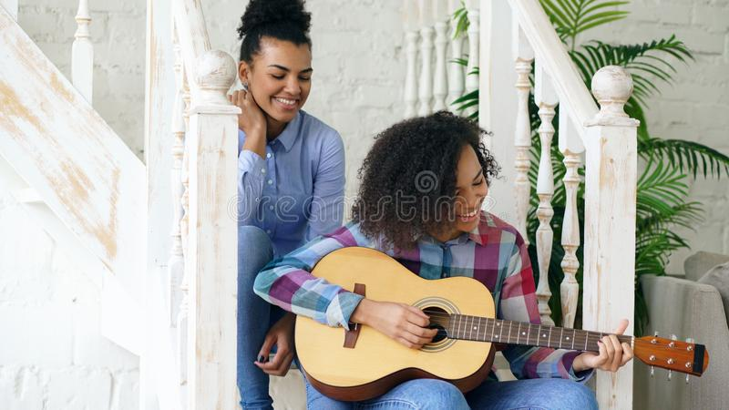 Two brazilian curly girls sistres sitting on stairs and practice to play acoustic guitar. Friends have fun and singing.  royalty free stock photo
