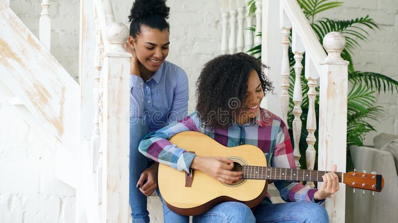 Two brazilian curly girls sistres sitting on stairs and practice to play acoustic guitar. Friends have fun and singing.  stock photos