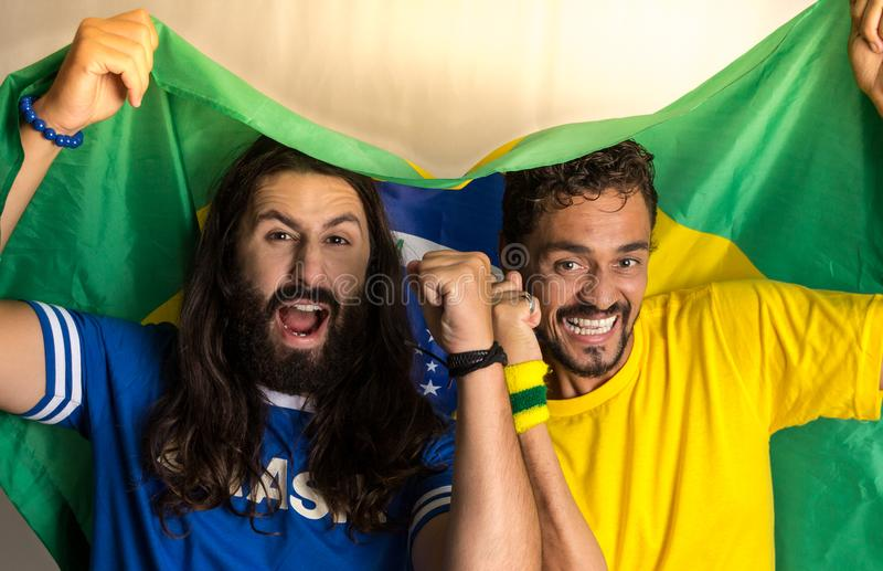 Two brazilian friends celebrating on soccer / football match on. Brazil supporters. Two brazilian friends celebrating on soccer / football match on white stock image