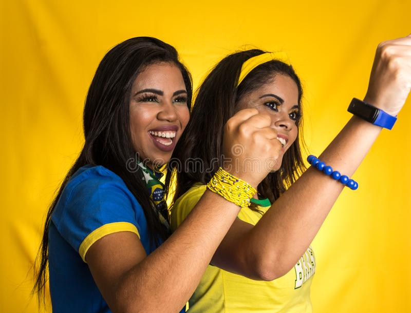 Two brazilian friends celebrating on soccer / football match on stock photos