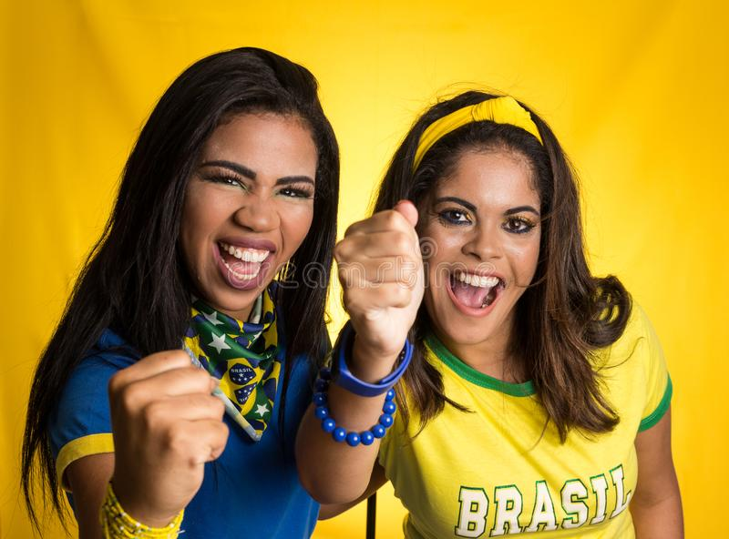 Two brazilian friends celebrating on soccer / football match on. Brazil supporters. Two brazilian friends celebrating on soccer / football match on yellow royalty free stock images
