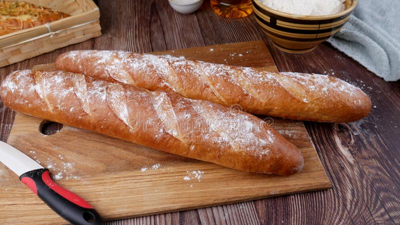Two bread baguettes on a cutting board on on a wooden table royalty free stock photos