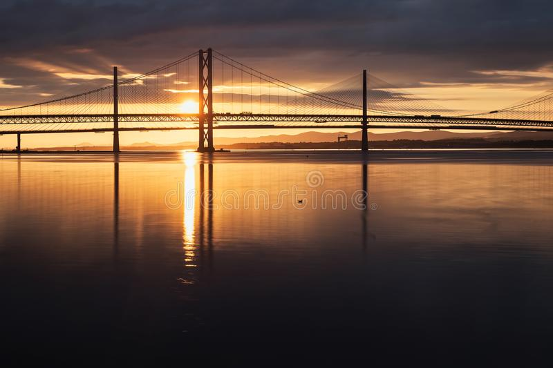 Two bridges against the setting sun and the sea. Forth Road Brtidge and Queensferry Crossing, Scotland, United Kingdom royalty free stock photography