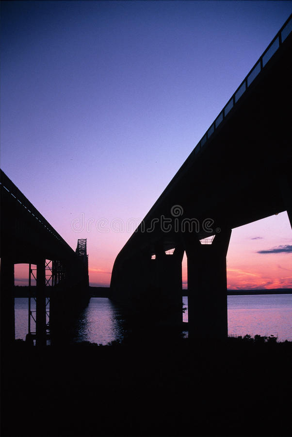 Two Bridges -- Jamestown, Rhode Island. The Old Jamestown Bridge stands next to its replacement, the Verazano Bridge at sunset royalty free stock images