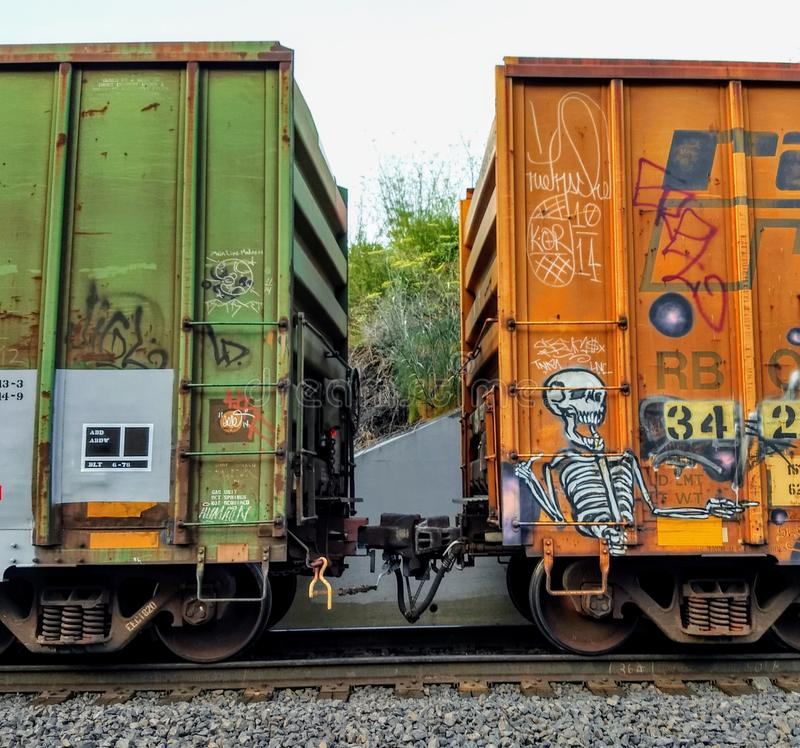 Two brightly colored and tagged railcars at there point of connection. Green, yellow, grafitti, train royalty free stock images