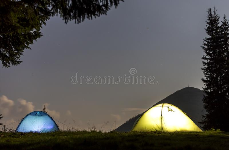 Two brightly lit tourist tents on green grassy forest clearing on dark mountain and clear blue starry sky copy space background. Tourism, night camping in royalty free stock image