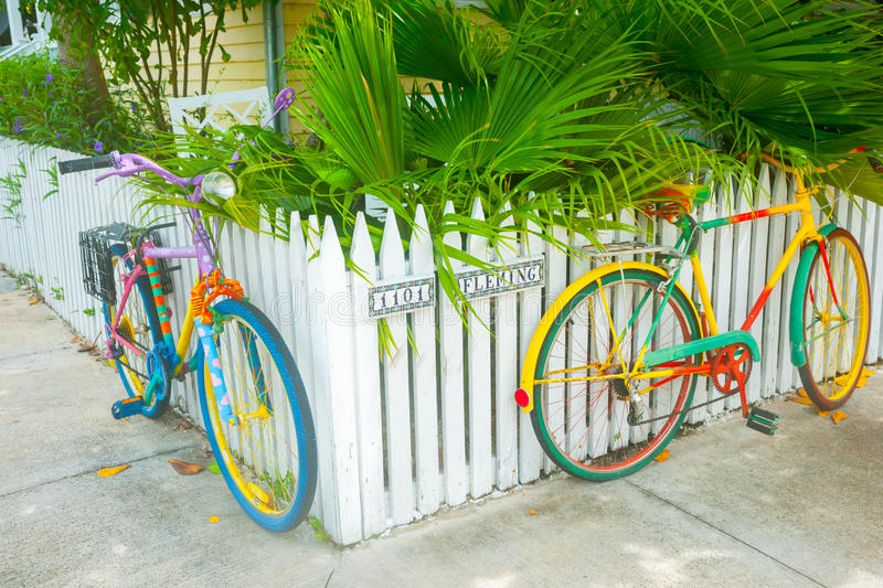 Two brightly painted bicycles leaning on picket fence on residential street corner royalty free stock photos