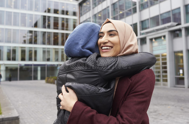 Two British Muslim Women Friends Meeting Outside Office royalty free stock image