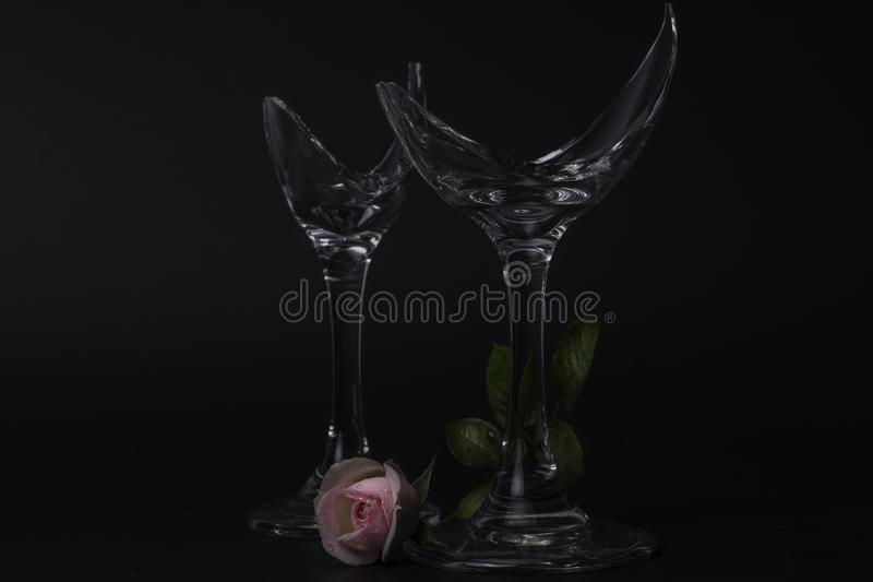 Two Broken Champagne Glasses with a pink rose stock photos