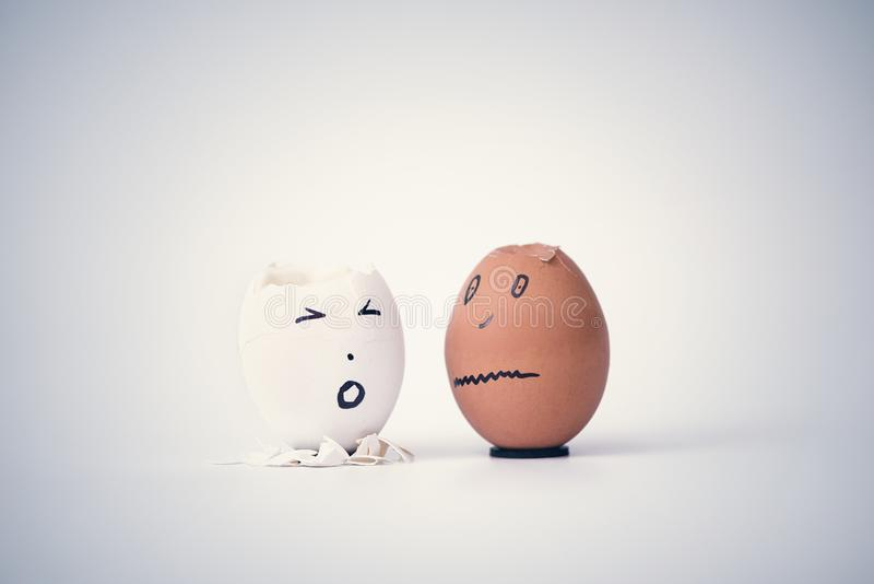 Two broken eggs in the form of human head white and black on a stand complain to each other. stock photos