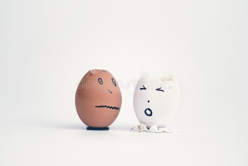 Two broken eggs in the form of human head white and black on a stand complain to each other. stock images