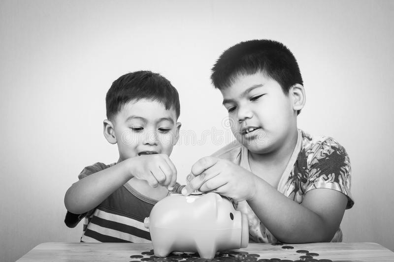 Two brother save money in piggy bank stock images