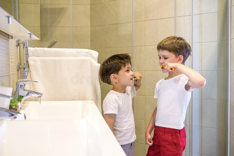 Two brothers brush my teeth in the bathroom.The beginning of a new day royalty free stock photography