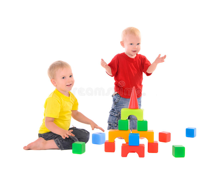Two brothers builds toy building of colored cubes stock photos