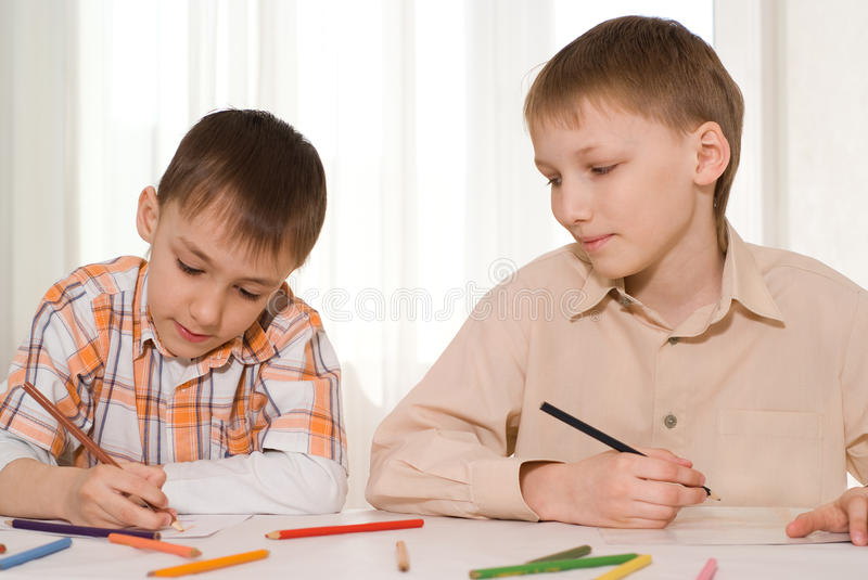Two brothers draw. Brothers sit at the table and draw stock images